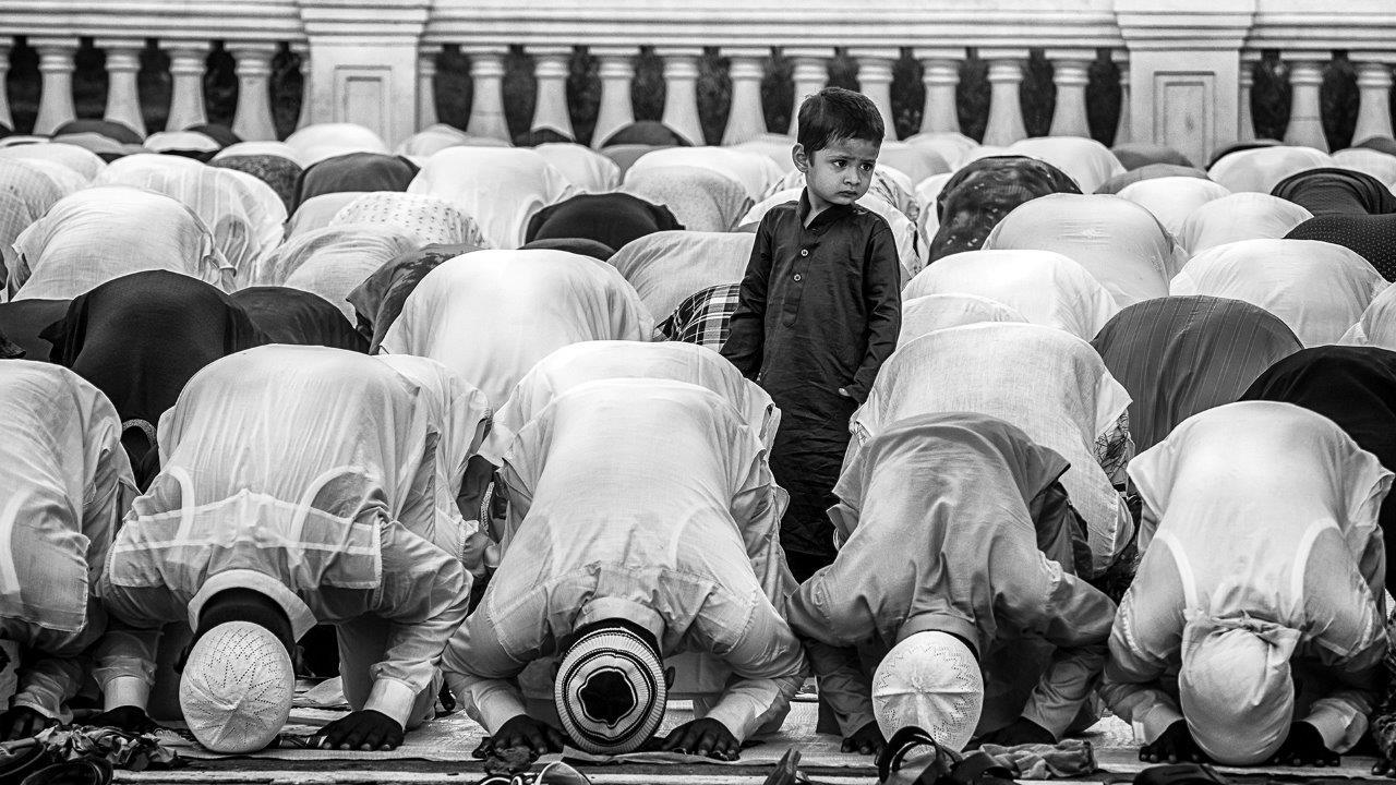 Zdjęcie konkursowe z wystawy pod tytułem Dziecko - Dziecko wśród grupy modlących się ludzi