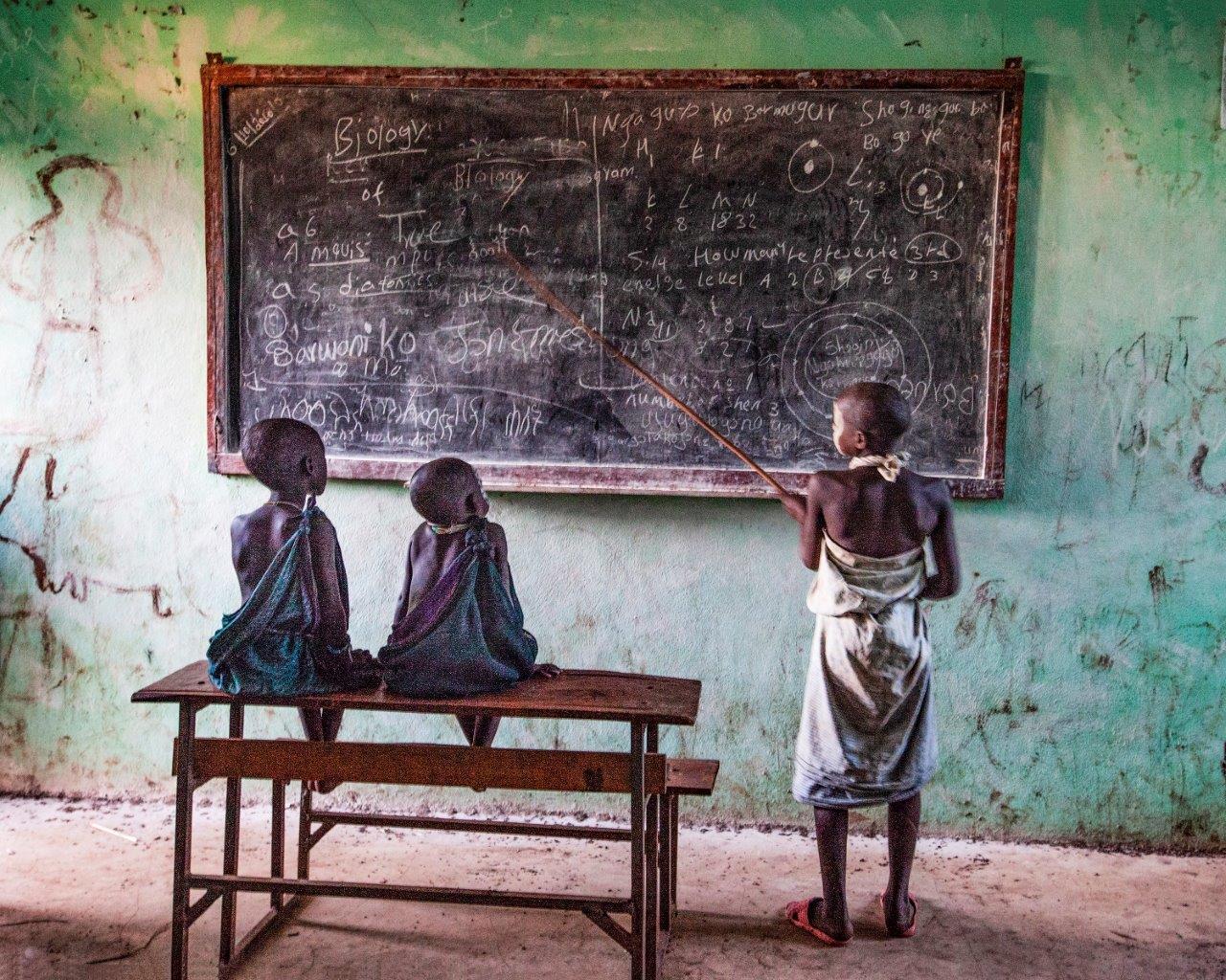Zdjęcie konkursowe z wystawy pod tytułem Dziecko - Trójka dzieci przy szkolnej tablicy