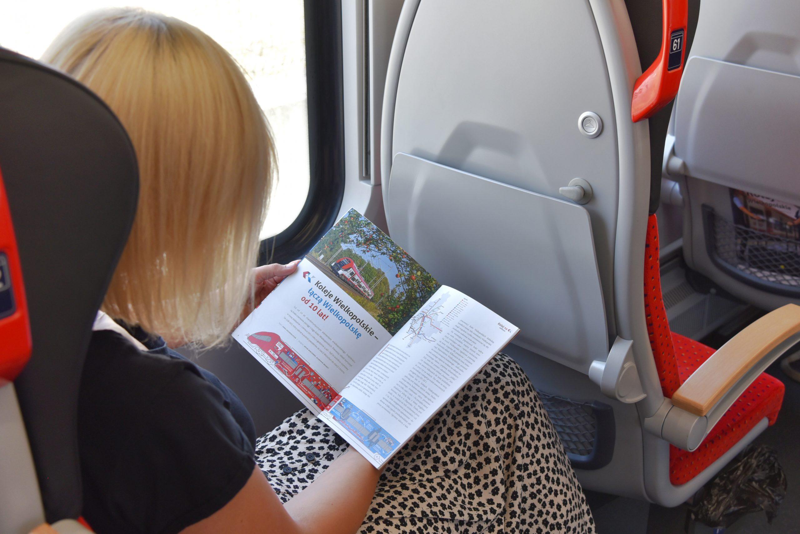 Pasażerka czytająca magazyn pokładowy KW w pociągu